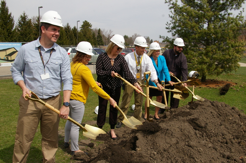 High school staff pose with gold shovels at ground breaking ceremony